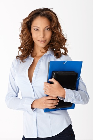 Attractive young woman holding folders, standing over white background. photo
