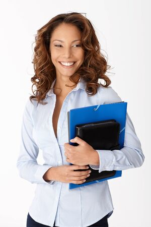 Beautiful young woman smiling holding folders, standing over white background. photo