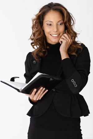 Attractive ethnic businesswoman talking on mobile phone, smiling, holding organizer in hand. photo