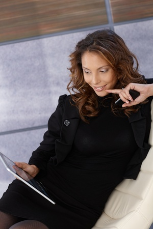 Young elegant woman using tablet computer, smiling. Stock Photo - 13061221