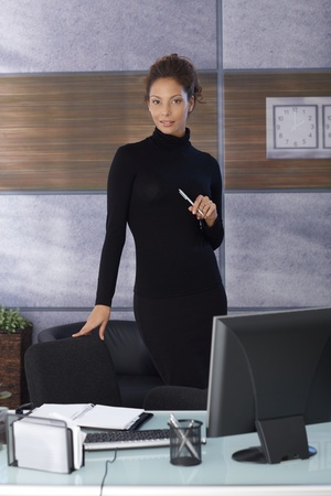 Pretty businesswoman standing by desk in office in black outfit. photo