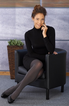 Attractive young elegant businesswoman sitting in armchair, talking on mobile phone, smiling. photo