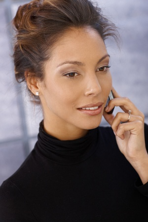 Portrait of attractive afro-american businesswoman on mobile phone in polo-neck sweater. photo
