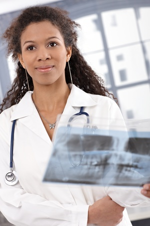 Portrait of attractive female doctor holding x-ray image, smiling. Stock Photo - 13070092