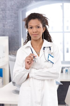 heal care: Portrait of attractive Afro-american female doctor in lab coat, smiling.