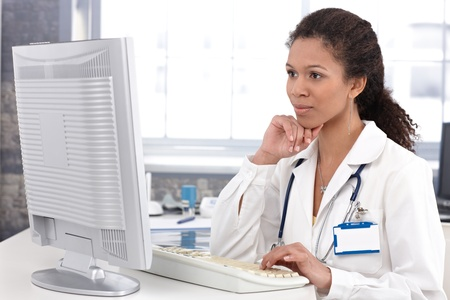 Afro-american female doctor sitting at desk working on computer. photo