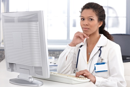 Portrait of young ethnic female doctor working on computer. photo