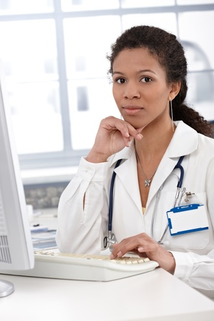 Portrait of attractive young female doctor working on computer in doctor's room. Stock Photo - 13068695