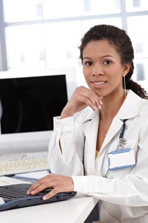 Cheerful female doctor working on computer, smiling, looking at camera. photo