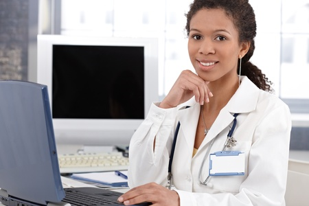 Smiling ethnic female doctor sitting at desk, working on laptop computer. Stock Photo - 13068223