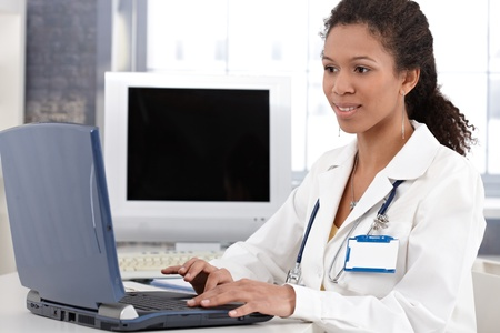 Young ethnic female doctor working on laptop computer, smiling. photo