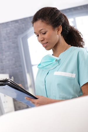 Afro-american young nurse working with case sheets, writing notes. Stock Photo - 13068975