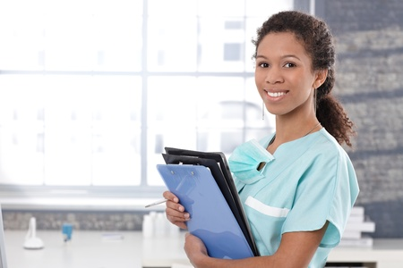 Happy afro medical worker holding case sheets, smiling. Stock Photo - 13068215