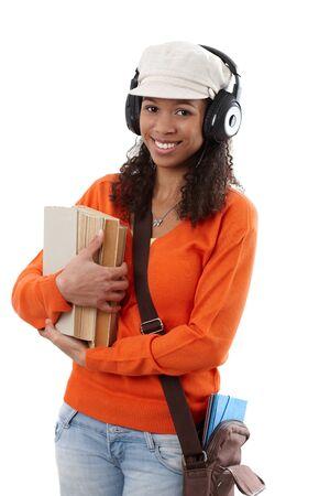 Happy ethnic student going to school with earphones, holding books. Stock Photo - 13068696
