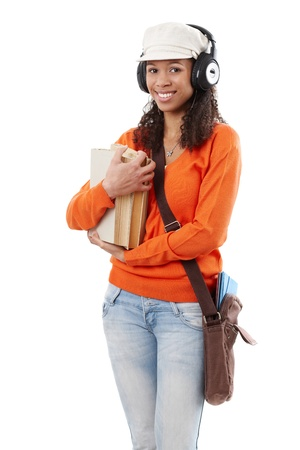 Afro student with books, earphones and shoulder bag heading to school. Stock Photo - 13068372