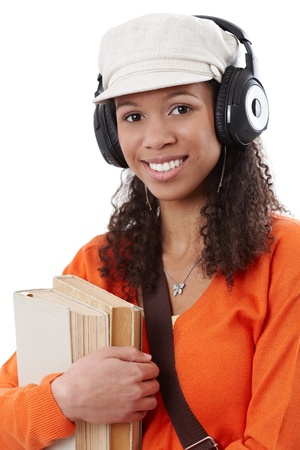 Smiling afro-american student heading to school, holding books, listening to music through earphones. Stock Photo - 13070601