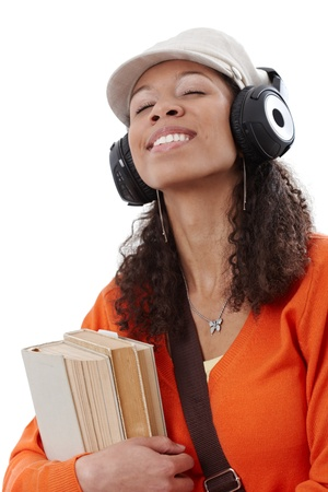 Ethnic girl enjoying music through earphones eyes closed while going to school with books in hand. Stock Photo - 13070222