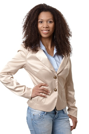 Casual ethnic woman smiling with hand on hip, wearing jeans and jacket. Stock Photo - 13068199