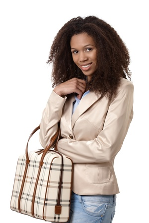 Attractive afro-american woman smiling, holding handbag. photo
