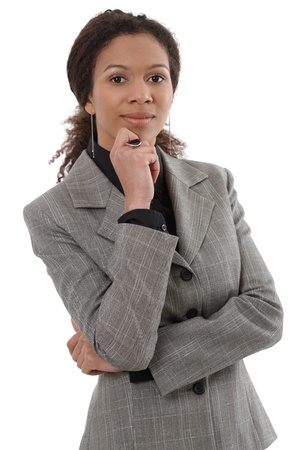 Portrait of smart ethnic businesswoman standing with hand on chin. photo
