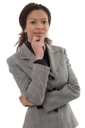 mujer sola: Retrato de la empresaria �tnica inteligente de pie con la mano en la barbilla.