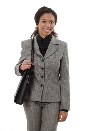 Happy businesswoman holding shoulder bag, smiling. photo