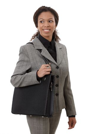 ethnic attire: Pretty afro businesswoman going to work, holding shoulder bag, smiling. Stock Photo