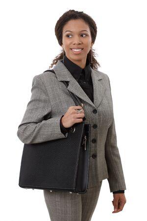 Pretty afro zakenvrouw naar het werk gaan, houden schoudertas met een glimlach. Stockfoto