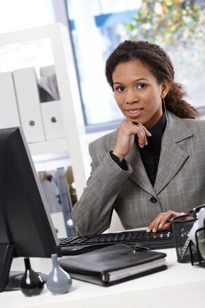 Attractive young afro-american businesswoman sitting at desk in bright office, working with computer. photo
