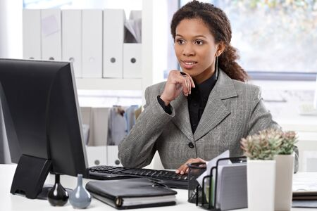 Attractive young afro businesswoman sitting at desk in bright office, using computer. photo