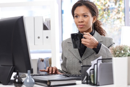 Young afro businesswoman at work in office, drinking tea, using computer. photo