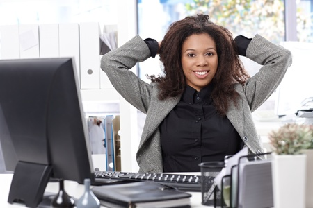 Smart afro businesswoman sitting at desk, smiling, hand in hair. photo