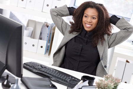 Beautiful afro businesswoman sitting at desk in office, smiling, stretching. photo
