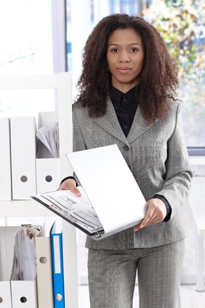 Pretty young afro-american businesswoman holding folder, standing in bright office. photo