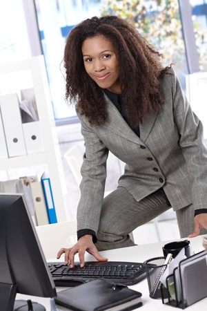 Attractive afro businesswoman working at desk in bright office, typing on keyboard, smiling. photo