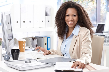executive office: Portrait of beautiful smiling afro-american office worker sitting at desk, using computer. Stock Photo
