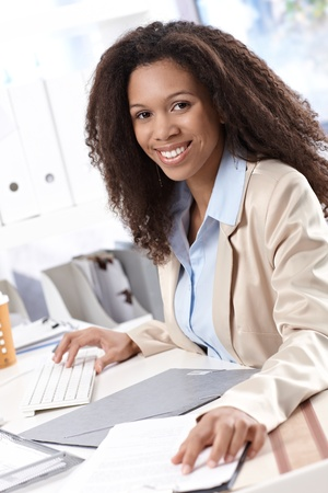 Happy afro-american businesswoman working at desk, using computer, smiling. photo