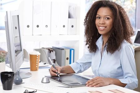 trabajador oficina: Sonriente joven afro-americano empleado de oficina con mesa de dibujo, sentado en el escritorio.