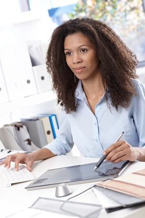 Attractive young afro engineer using drawing table at office, busy by working. photo