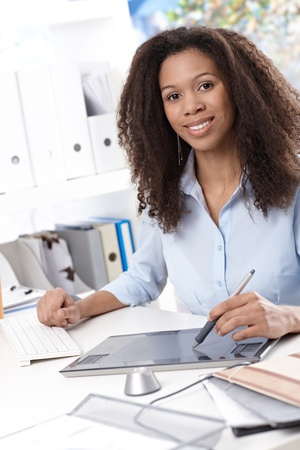 drawing pad: Smiling young businesswoman using drawing pad at desk. Stock Photo