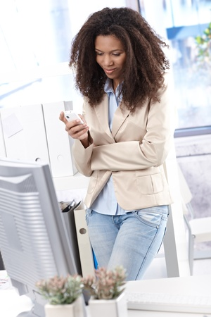 Pretty ethnic office worker texting on mobile phone, standing in office. photo