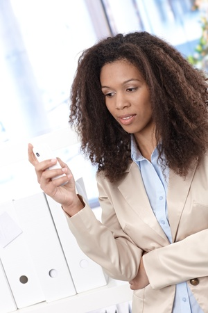 Young afro businesswoman texting on mobile phone in office. Stock Photo - 13070260