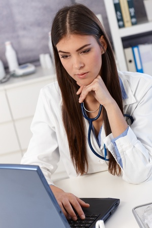 Young female doctor working on laptop computer in office. Stock Photo - 13098520