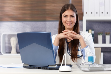 folded hands: Portrait of happy doctor sitting at office desk with hands folded smiling at camera. Stock Photo