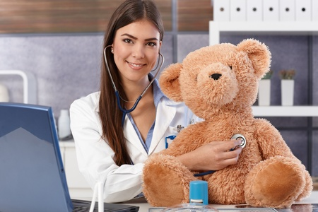 Smiling doctor examining teddy bear with stethoscope. photo