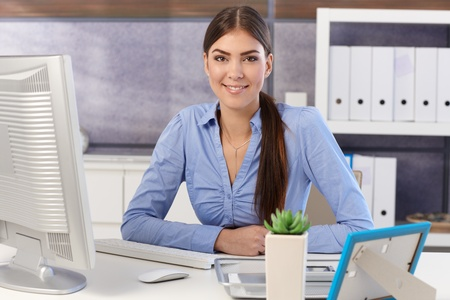 Portrait of young pretty businesswoman sitting at office desk, smiling. photo