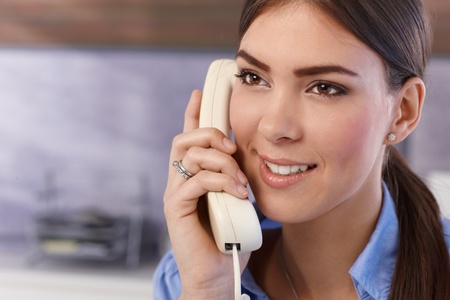 landline phone: Happy young pretty woman on landline phone call, smiling. Stock Photo