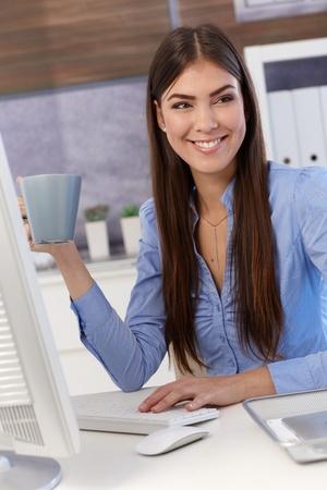 good shirt: Portrait of happy businesswoman drinking coffee at work, sitting at desk.