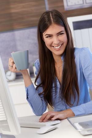 mujer tomando cafe: De negocios feliz sentado en el escritorio de oficina, de trabajo, la celebraci�n de taza de caf�, riendo. Foto de archivo