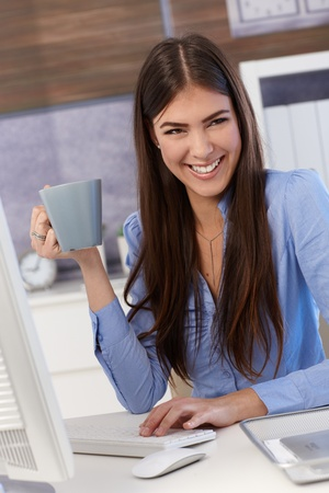 Happy businesswoman sitting at office desk, working, holding coffee mug, laughing. photo